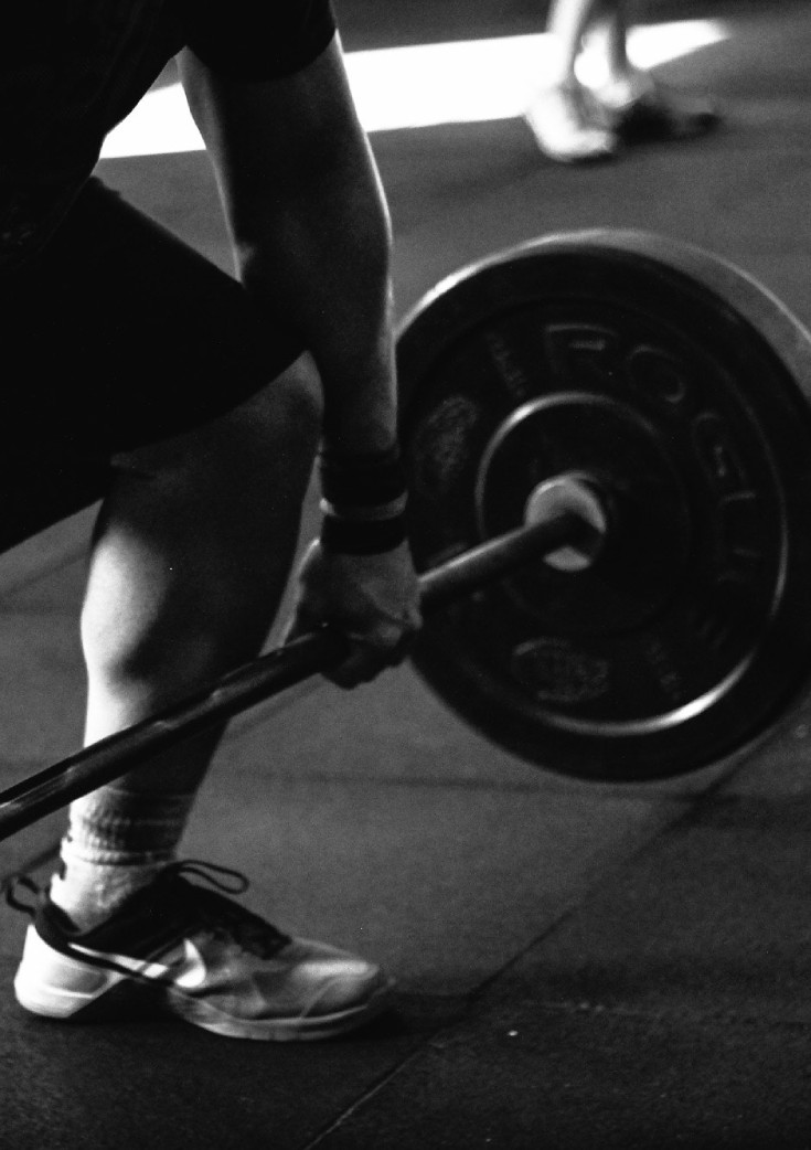Man dead-lifting barbell with weights