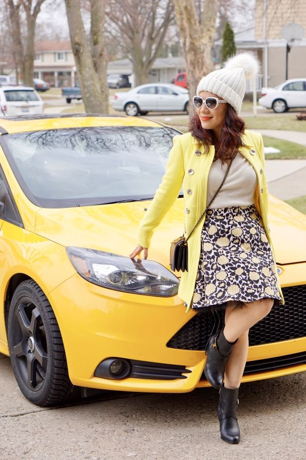 Yellow coat with cream top and floral skirt and black boots