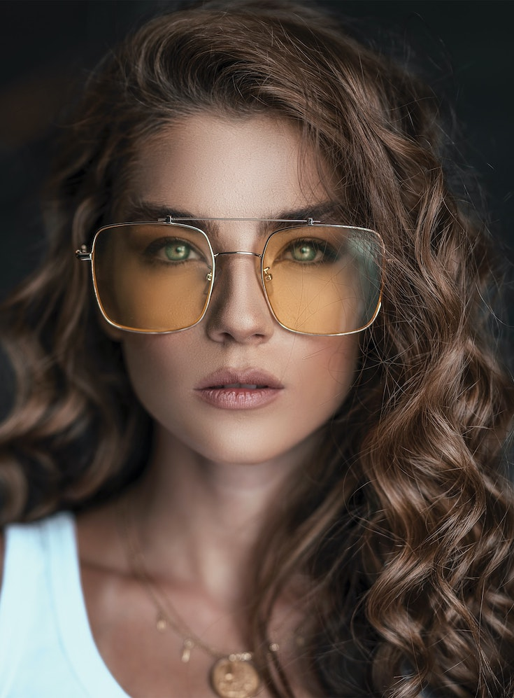 Girl with curly hear wearing large sunglasses