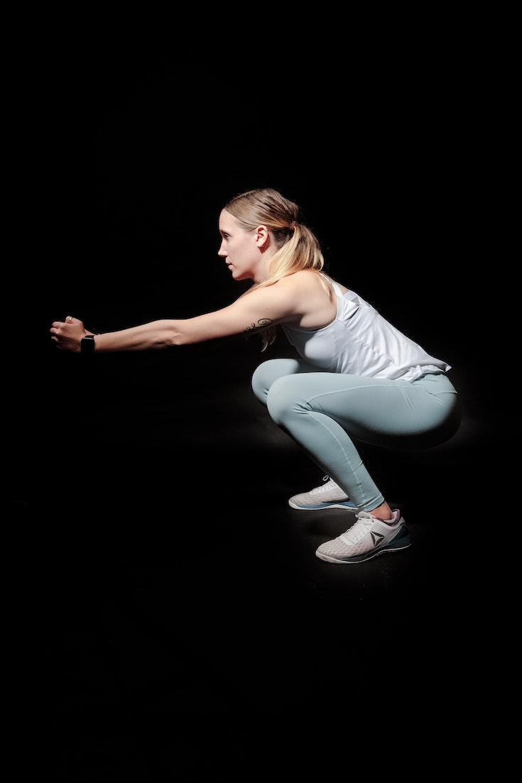 Woman performing deep squat, workout plan for the new year
