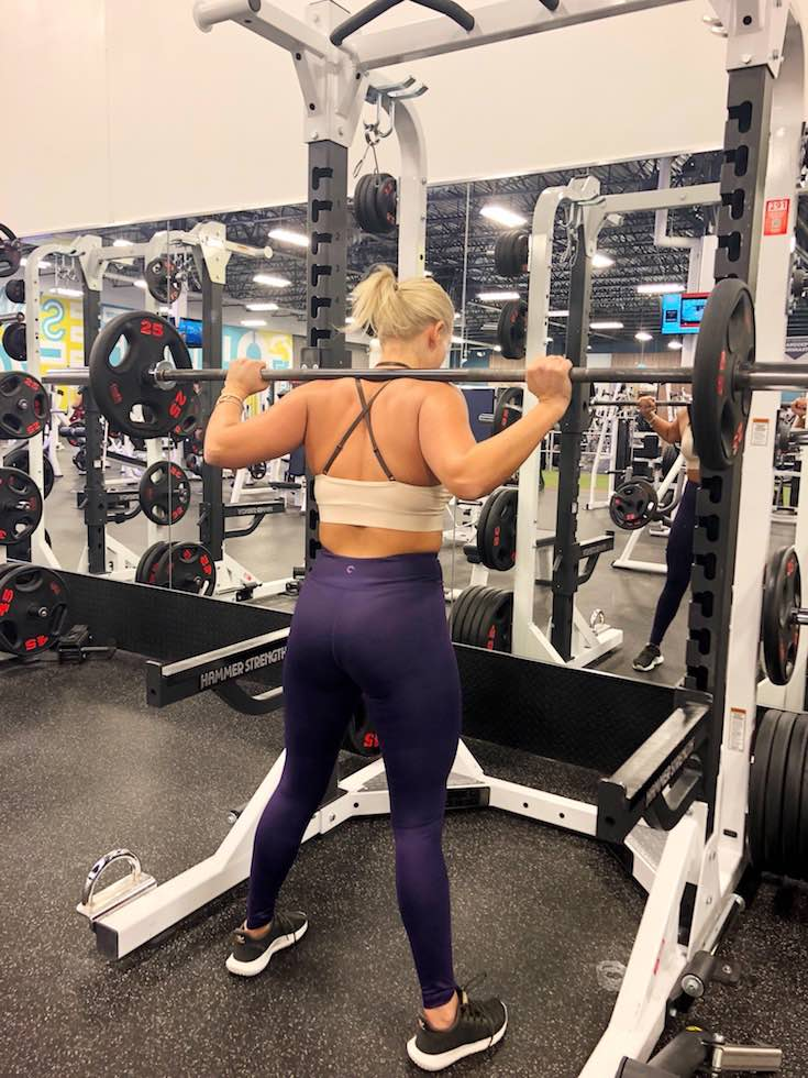 Exercise plan, Beige brown sportsbra top and purple yoga pants, woman on squat rack