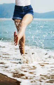 Woman in shorts splashing feet in the water
