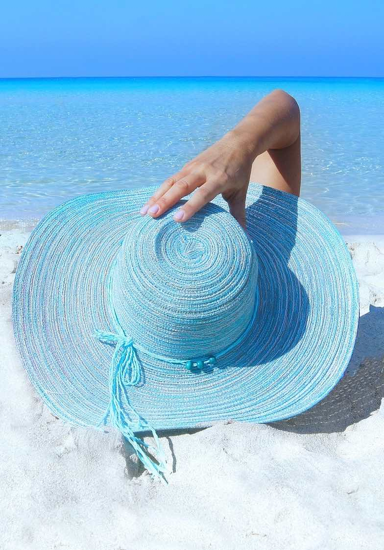 Woman on the beach with sun hat, cooling off from the heat