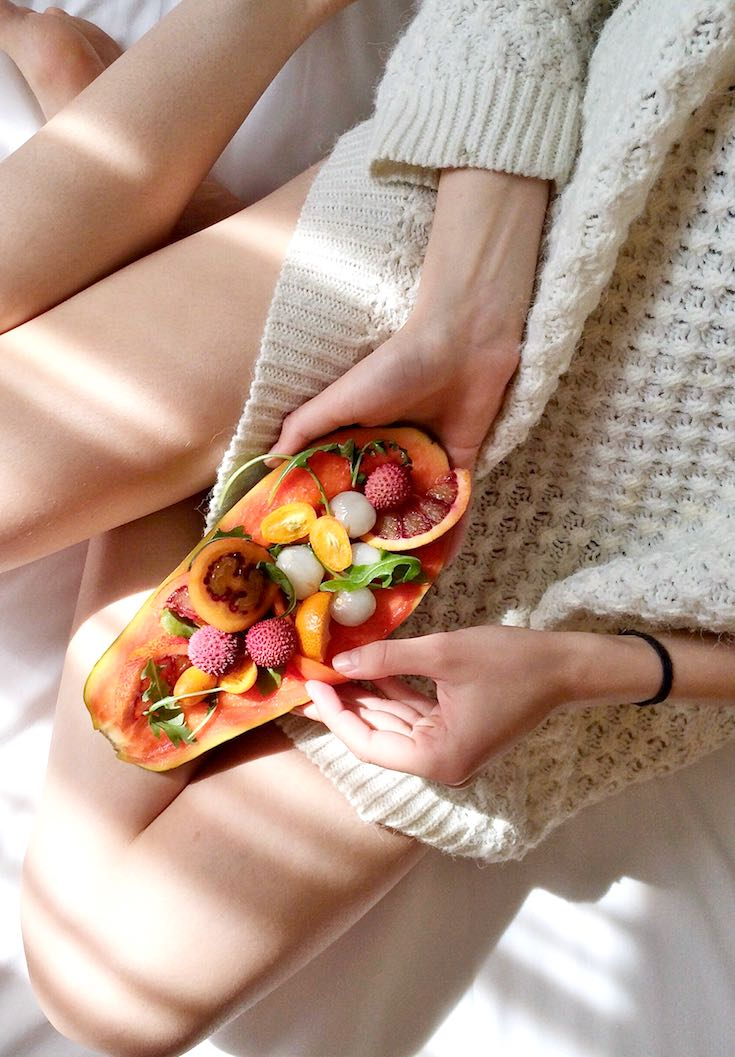 Woman eating healthy food on the bed