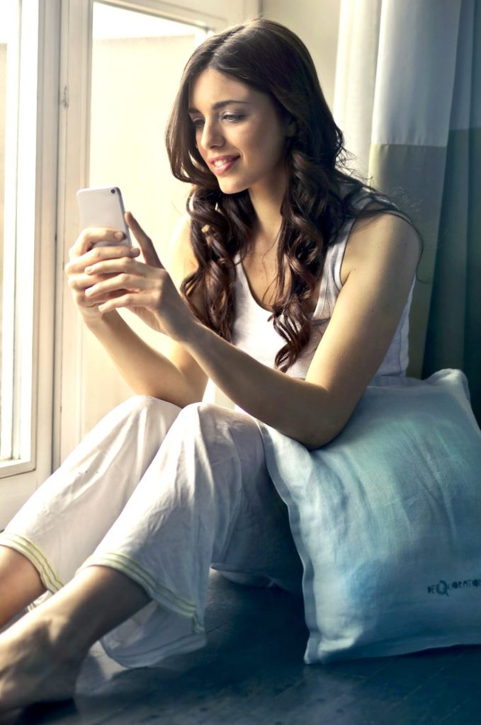 Woman looking at phone before bed