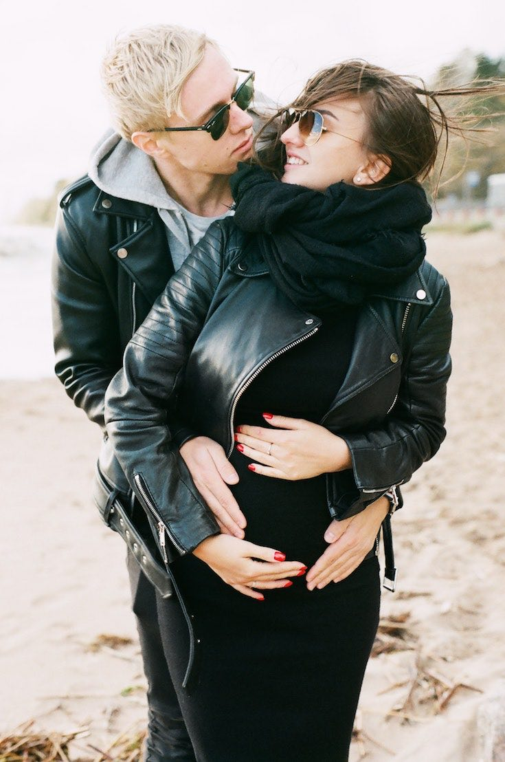 Pregnant woman in black dress, scarf and leather jacket with partner holding her from behind