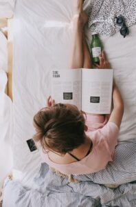 Woman sitting on bed reading a magazine