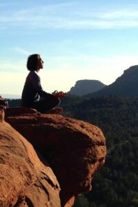 Wellness Pillars for Self-care, person meditating at the edge of mountain