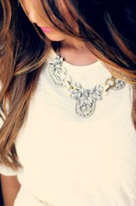 Woman wearing cocktail necklace on white top