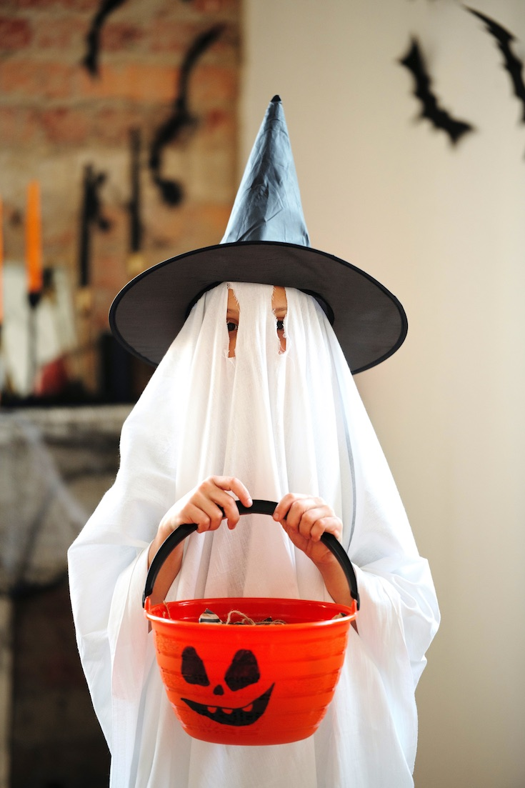 Child in ghost costume trick or treating