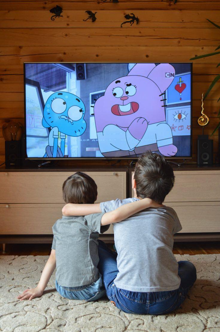 Siblings watching TV in entertainment room