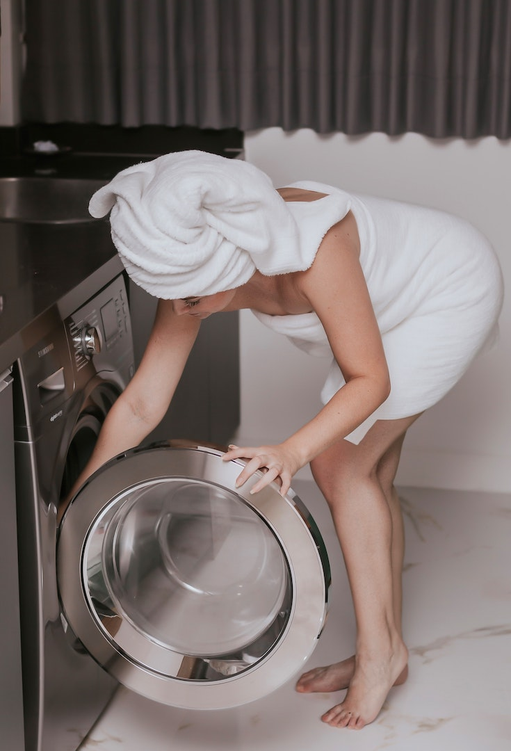 Woman in towel opening front loader washing machine