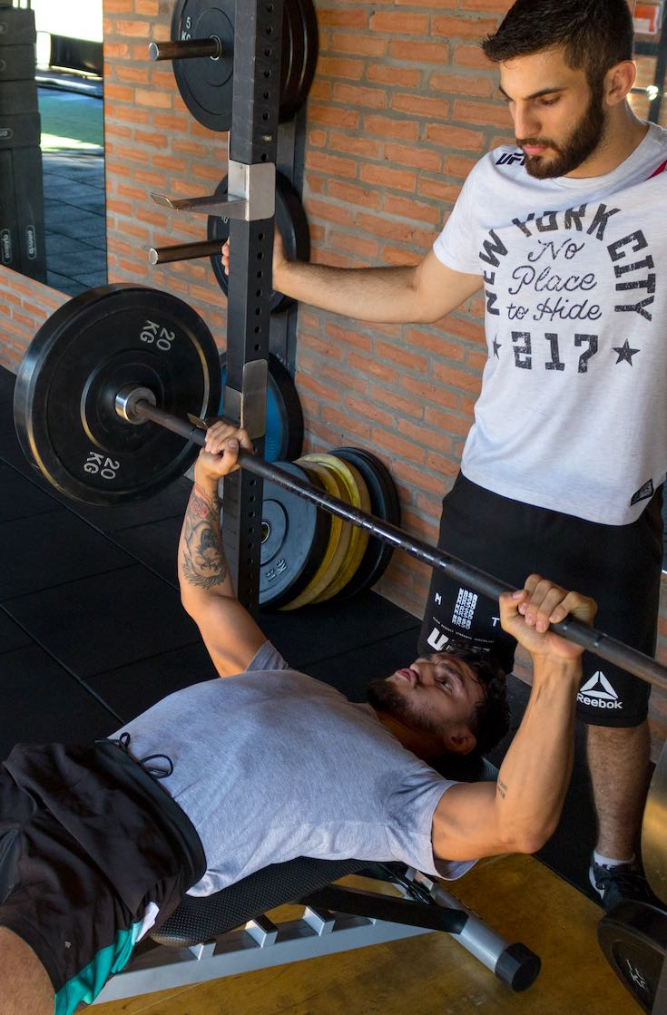 Fitness trainer supervising client on bench press_pin