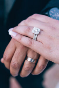 Couple's hands wearing wedding and engagement set of rings