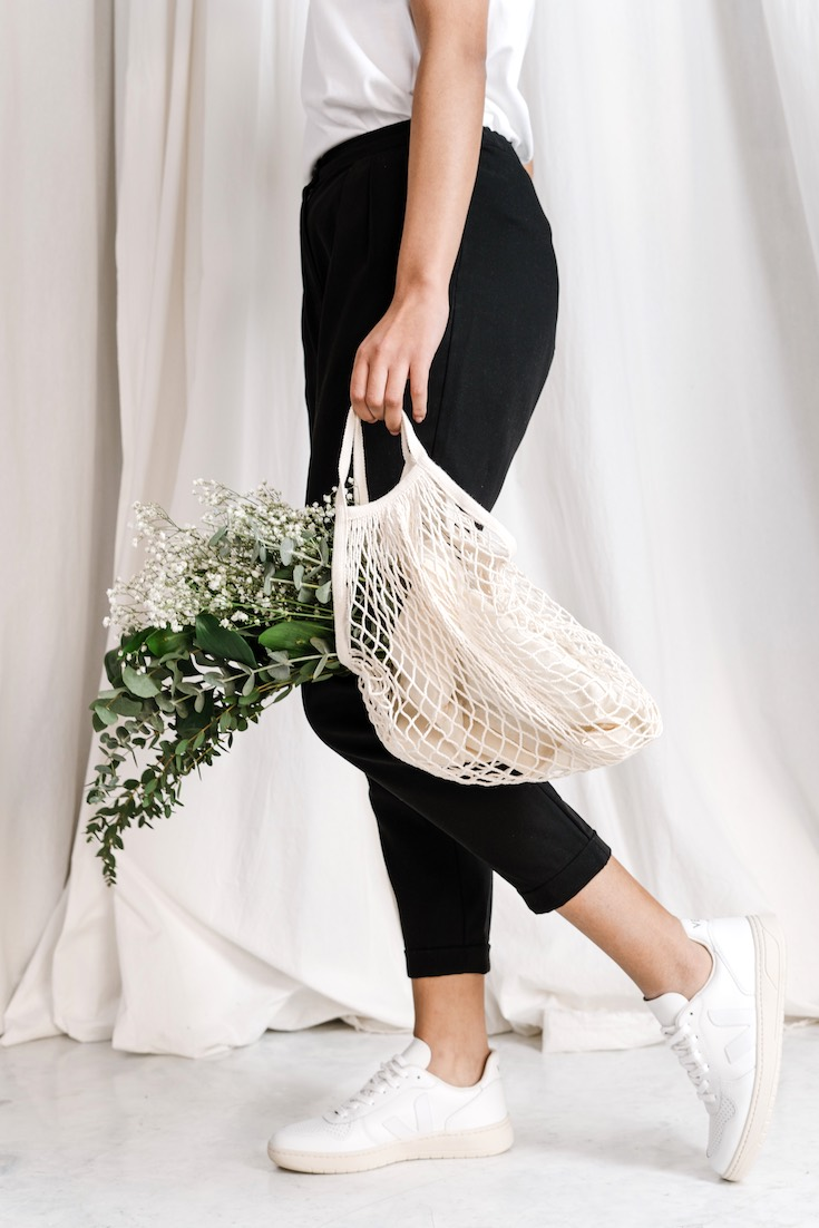 Woman in black pants holding net bag, zero-waste shopping