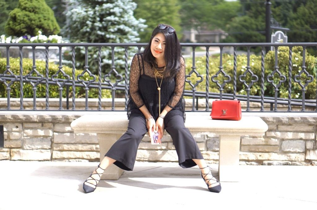 Grace in a black lace top and palazzo pants with laceup flats and a red purse