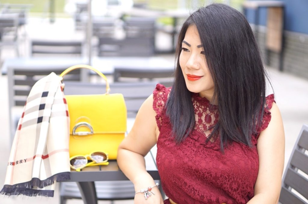 Grace in a wine red lace dress with a yellow purse and Burberry scarf