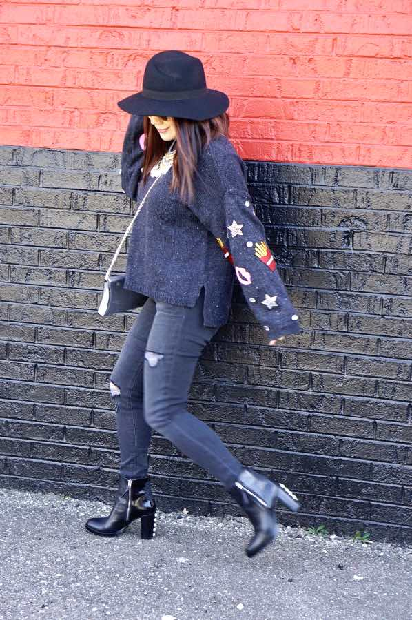 Patched navy sweater, skinny jeans and a black hat and boots