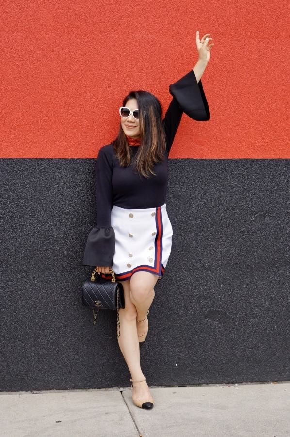 Black bell sleeve top, white wrap around skirt, nude pumps